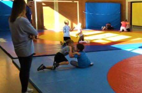 Raufen im Sportunterricht und die Lehrerin schaut zu